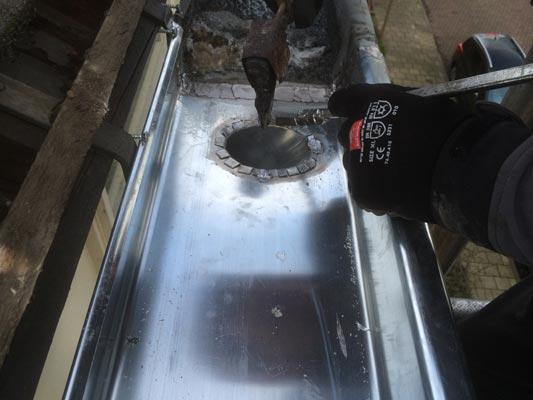 Robert van De Zinkspecialist is een zinken dakgoot aan het vervangen.